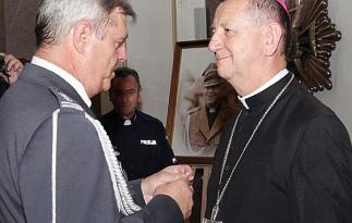 Prezes LOK Jerzy Salamucha odznacza biskupa Józefa Guzdka medalem 75‑lecia Ligi Obrony Kraju